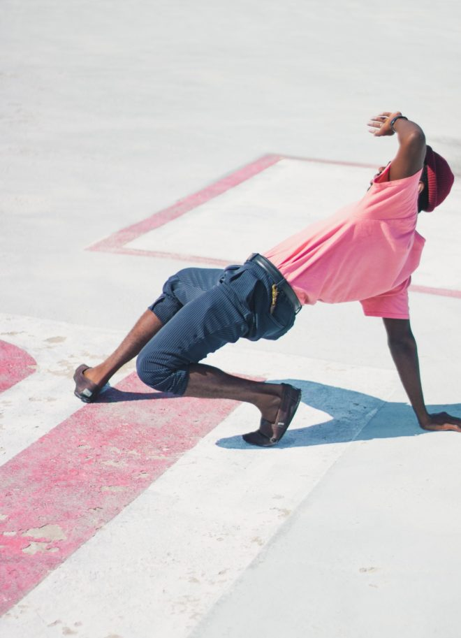 man wearing pink t-shirt doing dance move