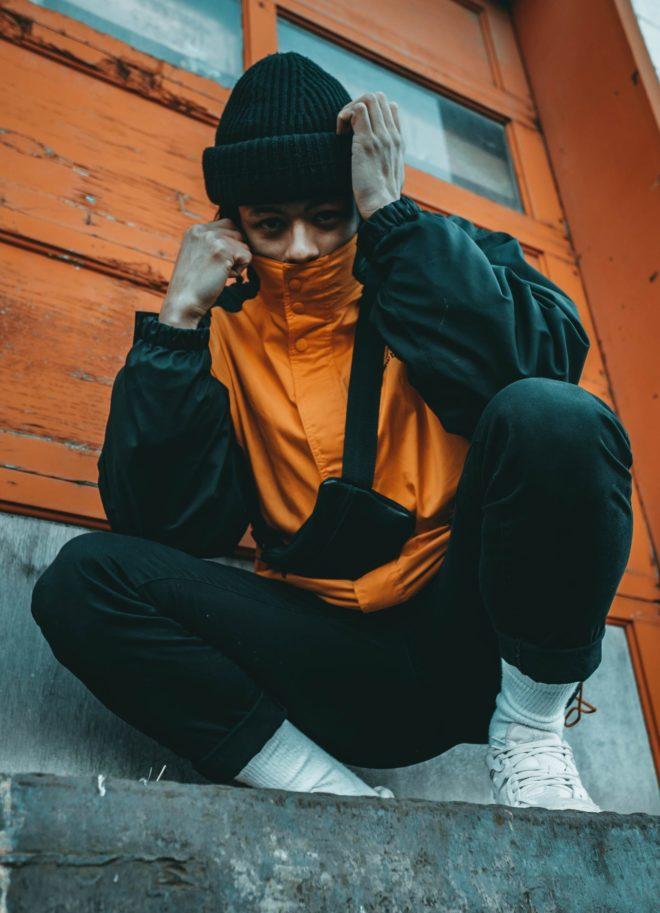 crouching man wearing orange and gray jacket beside wall