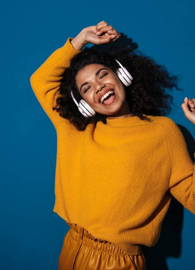 Woman posing isolated listening music with headphones.